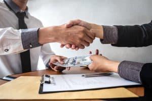 Businessman handshake with money of dollar banknotes in hands