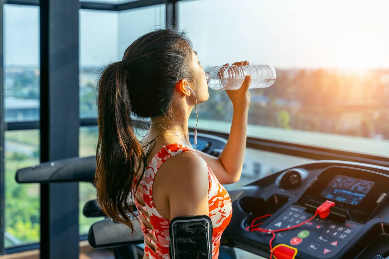 Young woman drinking water in the gym